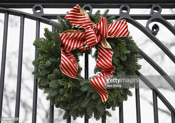 Christmas wreath is hung on a gate of the White House December 4 2013 in Washington DC US first lady Michelle Obama will host today military families...