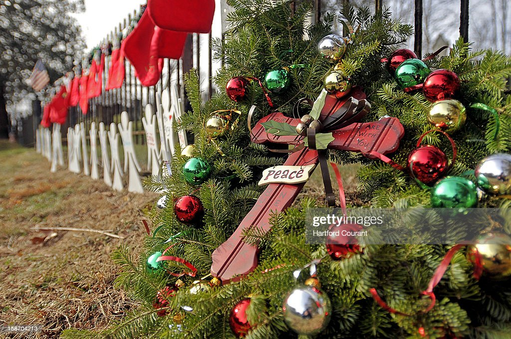 A Christmas wreath leans against a fence Monday, December 24, 2012, at the Sandy Hook Cemetery along with Christmas stockings and little angel cutouts in memory of the 26 people killed in the Sandy Hook Elementary School shooting in Newtown, Connecticut.
