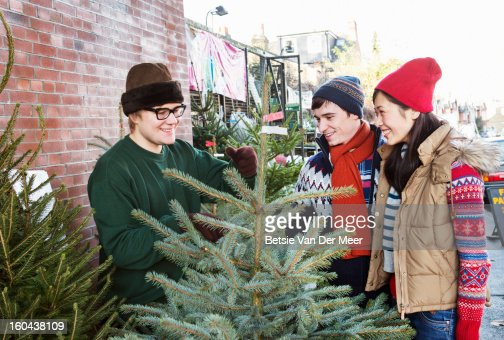 Christmastree salesman sells tree to couple. : Stockfoto