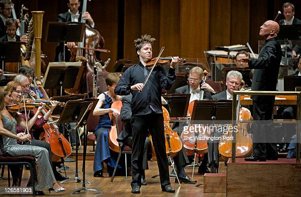 Christoph Eschenbach standing right directs the National Symphony Orchestra while guest soloist Joshua Bell performs Violin Concerto No 1 in G minor...