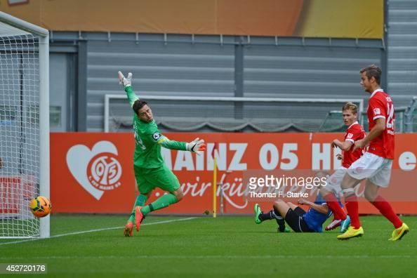 Christoph Hemlein of Bielefeld scores the winning goal against goalkeeper Bernhard Hendl of Mainz during the Third League match between FSV Mainz 05...