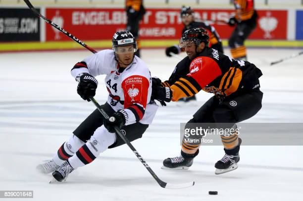 Christoph Hoehenleitner of Wolfsburg and Oliver Dame Malka of Bystrica battle for the puck during the Champions Hockey League match between Grizzlys...
