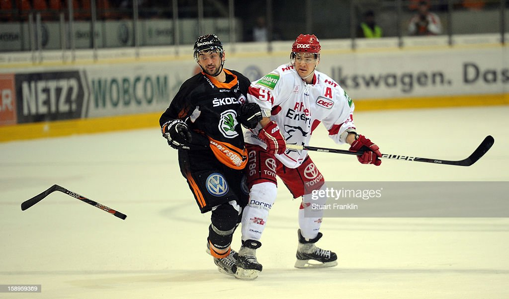 Christoph Hoehenleitner of Wolfsburg challenges for the puck with Moritz Mueller of Cologne during the DEL match between Grizzly Adams Wolfsburg and Kolner Haie at the Volksbank BraWo Eisarena on January 4, 2013 in Wolfsburg, Germany