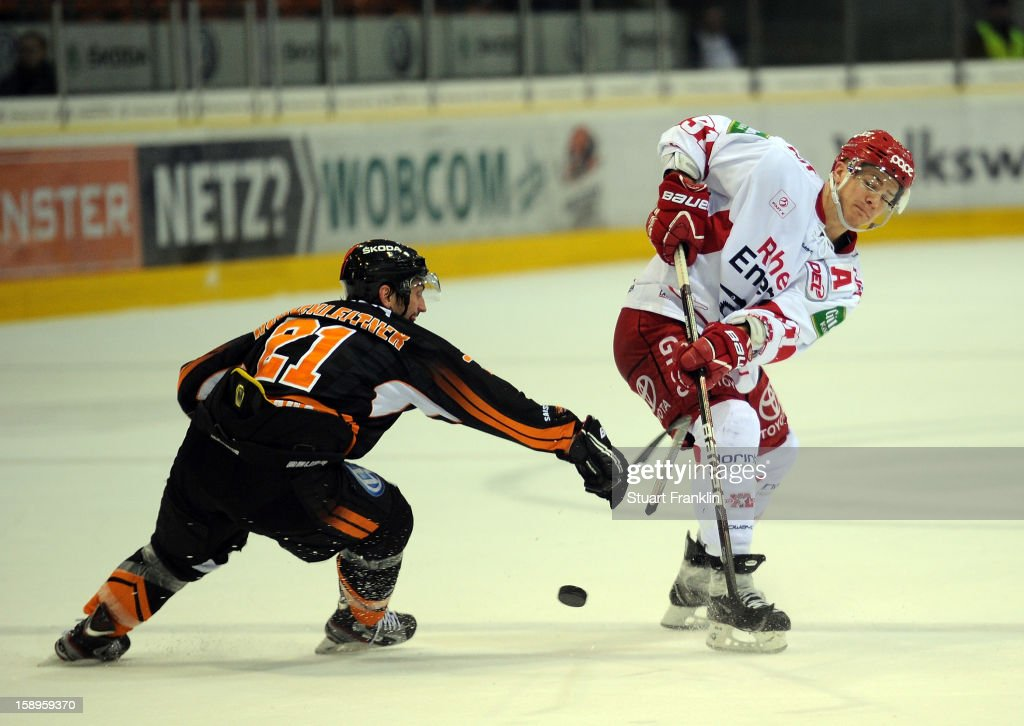 Christoph Hoehenleitner of Wolfsburg challenges for the puck with <a gi-track='captionPersonalityLinkClicked' href=/galleries/search?phrase=Moritz+Mueller&family=editorial&specificpeople=853045 ng-click='$event.stopPropagation()'>Moritz Mueller</a> of Cologne during the DEL match between Grizzly Adams Wolfsburg and Kolner Haie at the Volksbank BraWo Eisarena on January 4, 2013 in Wolfsburg, Germany