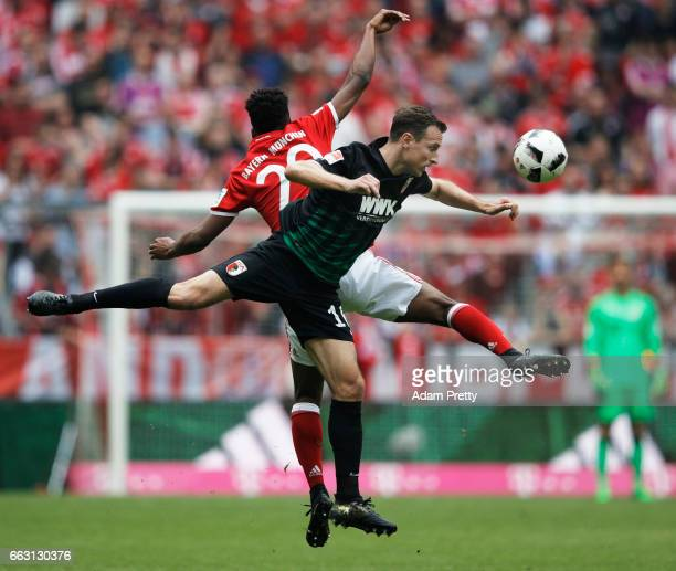Christoph Janker of Augsburg is challenged by Kingsley Coman of Bayern Munich during the Bundesliga match between Bayern Muenchen and FC Augsburg at...