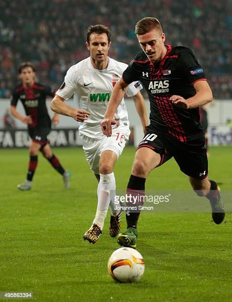 Christoph Janker of Augsburg vies with Markus Henriksen of Alkmaar during the UEFA Europa League group L football match FC Ausburg vs AZ Alkmaar at...