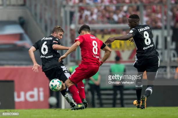 Christoph Kramer and Denis Zakaria of Borussia Moenchengladbach and Milos Jojic of 1FC Koeln battle for the ball during the Bundesliga match between...