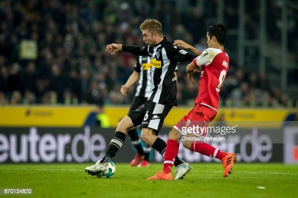 Christoph Kramer of Borussia Moenchengladbach is chased by Yoshinori Muto of FSV Mainz 05 during the Bundesliga match between Borussia...