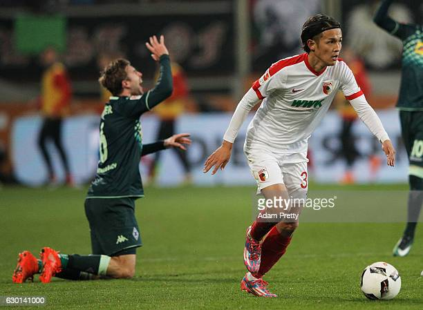Christoph Kramer of Borussia Moenchengladbach is injured by Takashi Usami of Augsburg during the Bundesliga match between FC Augsburg and Borussia...