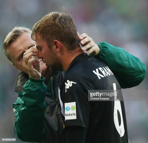 Christoph Kramer of Moenchengladbach gets treated for an injury by Dr Stefan Hertl during the Bundesliga match between Borussia Moenchengladbach and...