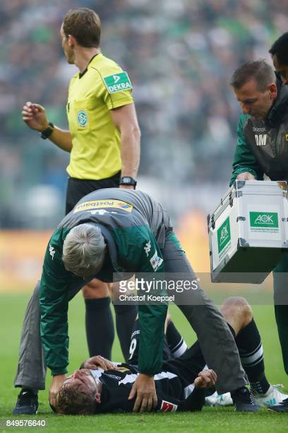Christoph Kramer of Moenchengladbach lies on the pitch injured and is looked after by the medics during the Bundesliga match between Borussia...