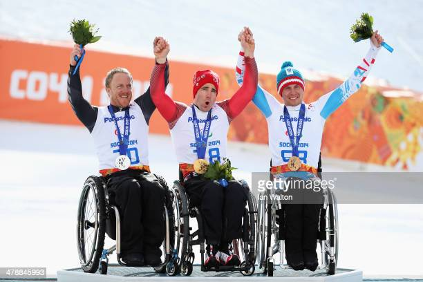 Christoph Kunz of Switzerland celebrates winning the gold medal with silver medalist Corey Peters of New Zealand and bronze medalist Roman Rabl of...
