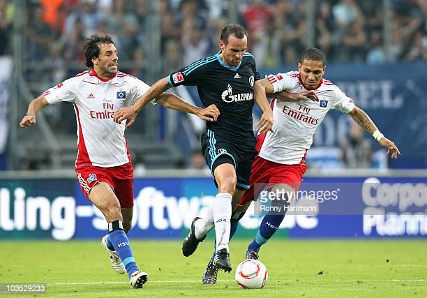 Christoph Metzelder of Schalke 04 battles for the ball with Ruud van Nistelrooy and Jermaine Jones of Hamburg during the Bundesliga match between...