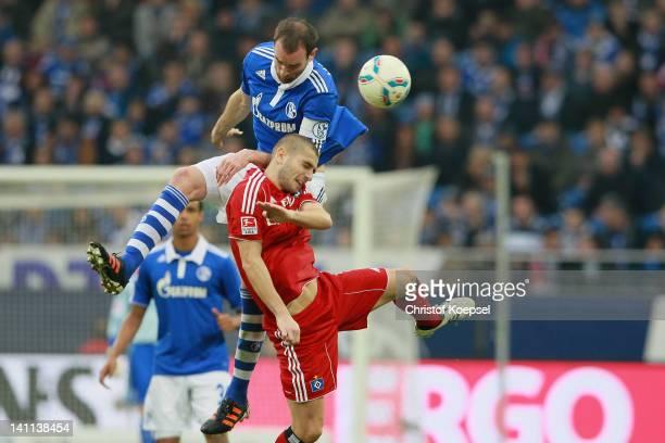 Christoph Metzelder of Schalke and Mladen Petric of Hamburg go up for a header during the Bundesliga match between FC Schalke 04 and Hamburger SV at...