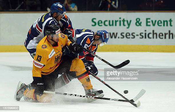 Christoph Schubert of Germany race for the puck against Milan Bartovic of Slovakia and his team mate Roman Kukumberg during the 3rd match of the...