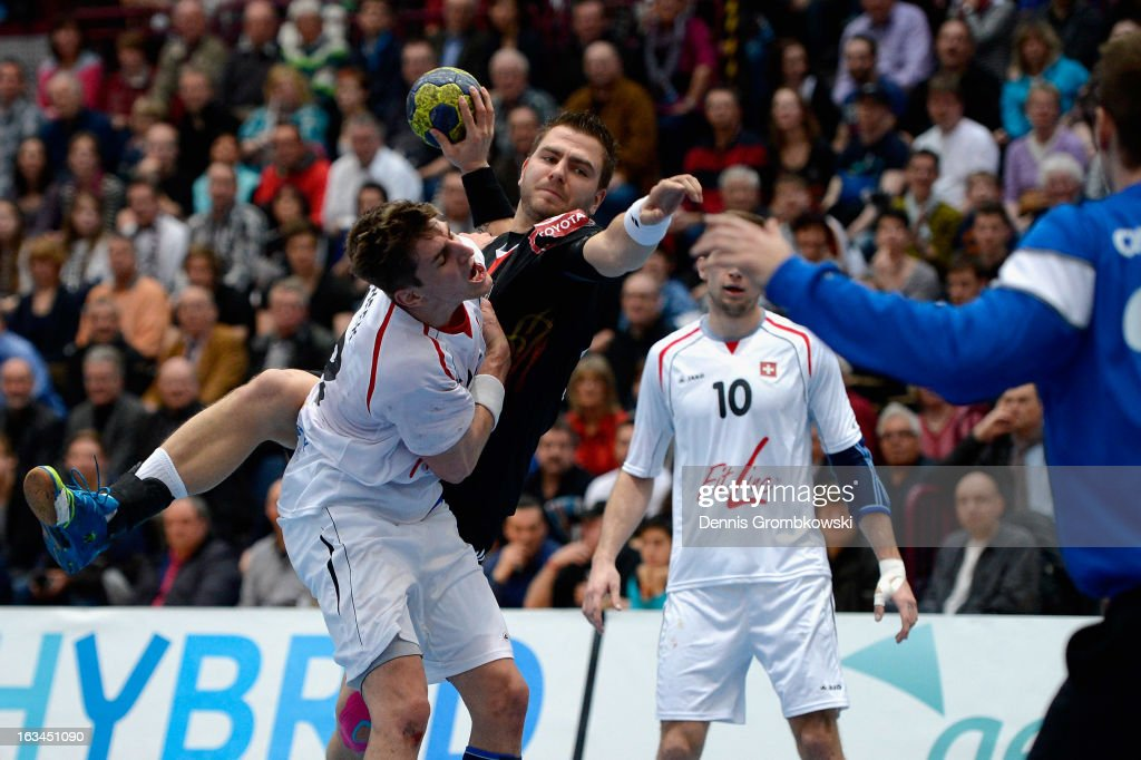 Christoph Theuerkauf of Germany scores under the pressure of Thomas Heer of Switzerland during the DHB International Friendly match between Germany and Switzerland at Conlog-Arena on March 10, 2013 in Koblenz am Rhein, Germany.