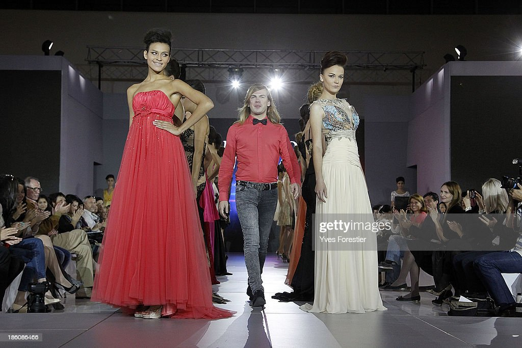 Christophe Guillarme surrounded by models walks on the catwalk at the end of his fashion show as part of the Art Style UZ 2013 at The Youth Art Palace on October 25, 2013 in Tashkent, Uzbekistan.