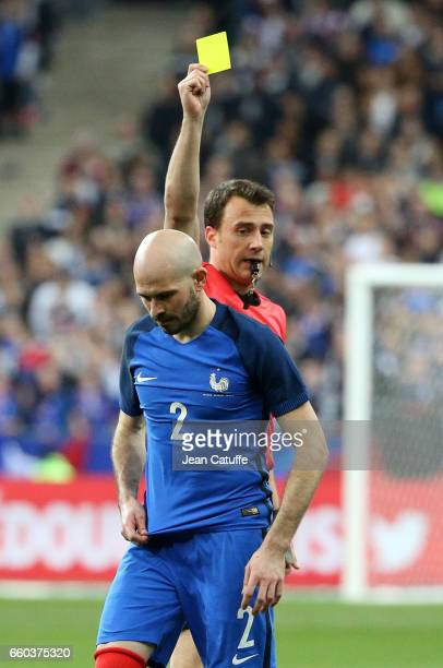 Christophe Jallet of France receives a yellow card from referee Felix Zwayer of Germany during the international friendly match between France and...