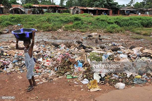 Christophe PARAYRE A child carries a tub near roadside garbage in Kamsar on October 24 2008 The village surrounded by mangroves has developed rapidly...