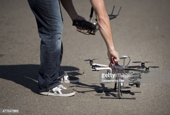 Christopher Brown coowner of Next New Homes Group reaches for his multirotor helicopter drone after taking aerial video of a home in Sacramento Calif...
