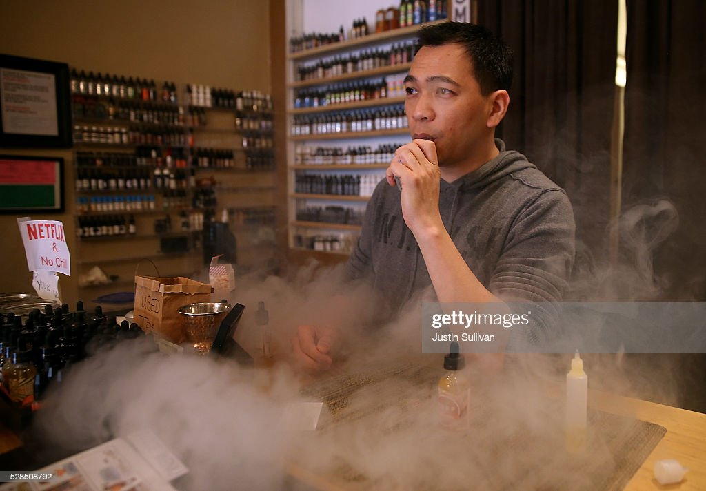 Christopher Chin blows puffs on an e-cigarette as he waits for customers at Gone With the Smoke Vapor Lounge on May 5, 2016 in San Francisco, California. The U.S. Food and Drug Administration announced new federal regulations on electronic cigarettes that will be the same as traditional tobacco cigarettes and chewing tobacco.