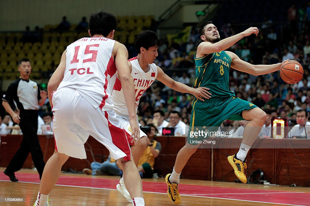 Christopher Goulding (R) of the Boomers brings the ball up the court with Li Xiaoxu and Zhou Peng (L) of China during game three of the series between the Australian Boomers and China at Tianjin Sports Center on June 12, 2013 in Tianjin, China.