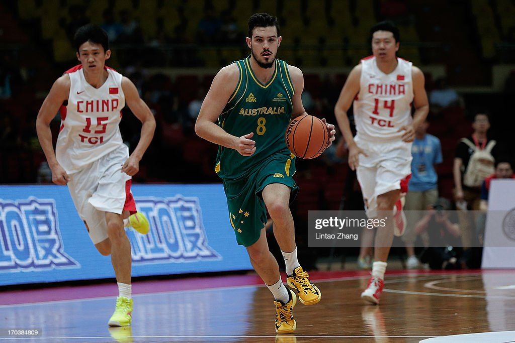 Christopher Goulding #8 of the Boomers brings the ball up the court with Wang Zhizhi (R) and Zhou Peng of China during game three of the series between the Australian Boomers and China at Tianjin Sports Center on June 12, 2013 in Tianjin, China.