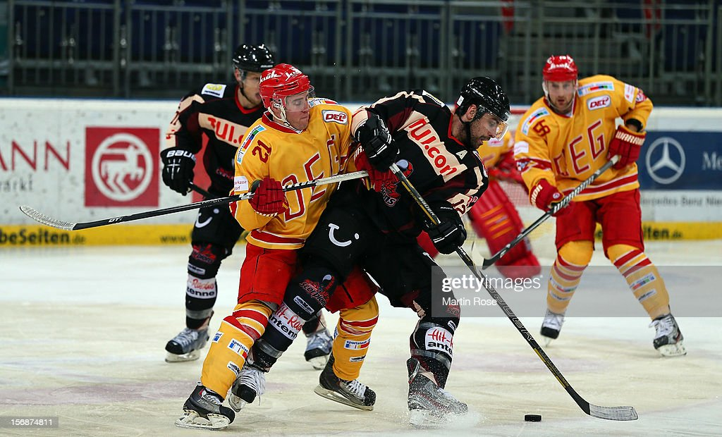 Christopher Herperger (R) of Hannover and Justin Bostrom (L) of Duesseldorf battle for the puck during the DEL match between Hannover Scorpions and Duesseldorfer EG at TUI Arena on November 23, 2012 in Hanover, Germany.