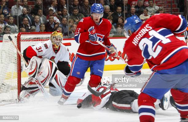 Christopher Higgins of the Montreal Canadiens takes a shot on Alex Auld of the Ottawa Senators as Alex Tanguay of the Montreal Canadiens battles in...