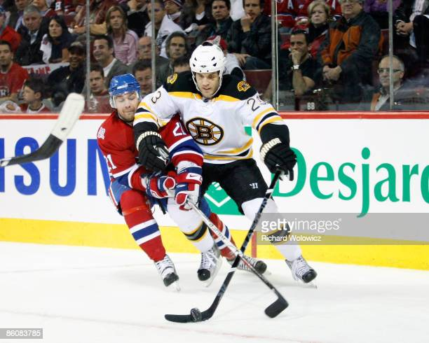 Christopher Higgins of the Montreal Canadiens tries to strip the puck from Steve Montador of the Boston Bruins during Game Three of the Eastern...
