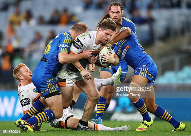 Christopher Lawrence of the Tigers is tackled by the Eels defence during the round 21 NRL match between the Parramatta Eels and the Wests Tigers at...