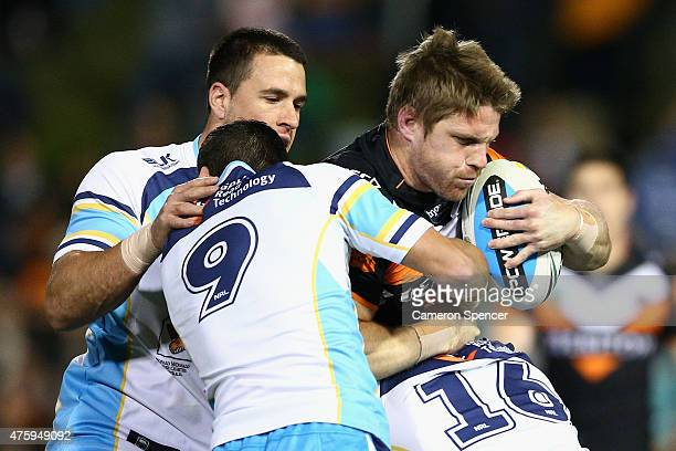 Christopher Lawrence of the Tigers is tackled during the round 13 NRL match between the Wests Tigers and the Gold Coast Titans at Leichhardt Oval on...