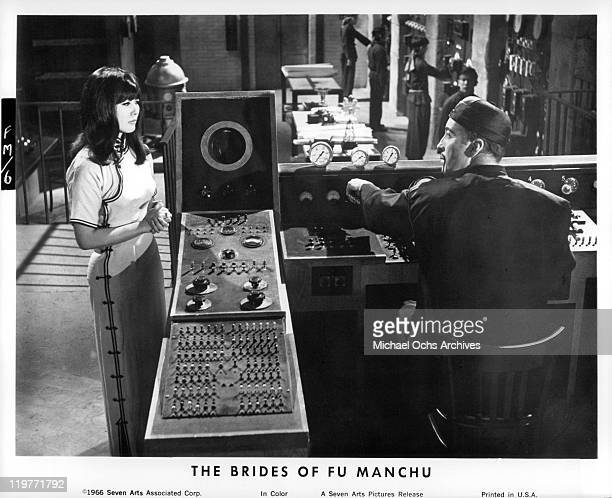 Christopher Lee at control board with actress in a scene from the film 'The Brides of Fu Manchu' 1966