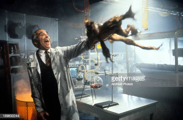 Christopher Lee attempts to thrown a gremlin off of his arm in a scene from the film 'Gremlins 2 The New Batch' 1990