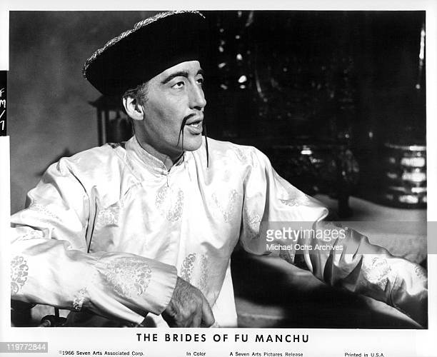 Christopher Lee sitting and talking in a scene from the film 'The Brides of Fu Manchu' 1966