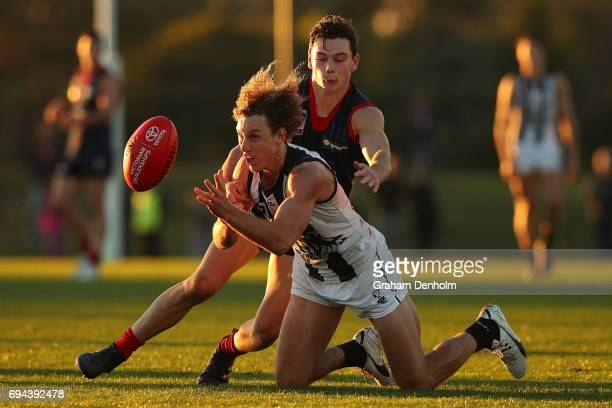Christopher Mayne of Collingwood handballs as he is tackled by Dion Johnstone of the Casey Demons during the round eight VFL match between Casey...