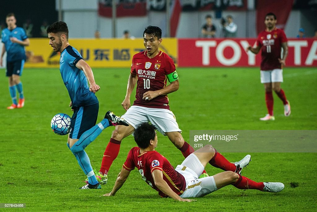 Christopher Naumoff (L) of Sydney FC controls the ball past Zheng Zhi (back) of China's Guangzhou Evergrande during their AFC Champions League group stage football match in Guangzhou, in China's Guangdong province on May 3, 2016. / AFP / STR