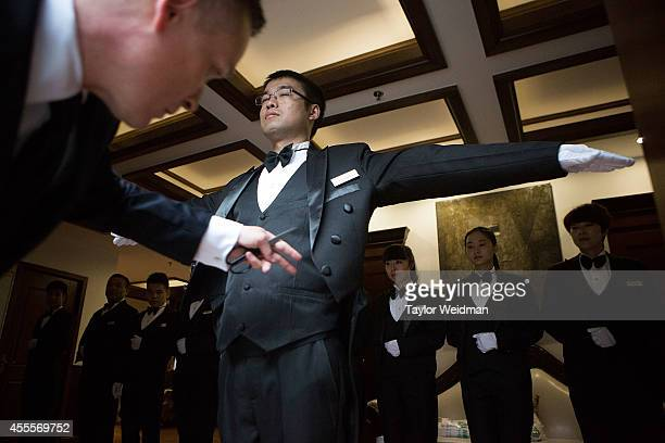 Christopher Noble an instructor at The International Butler Academy China inspects a butlery students uniform on September 16 2014 in Chengdu China...