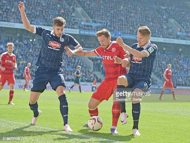 Christopher Noethe and Sebastian Schuppan of Bielefeld tackle Adam Bodzek of Duesseldorf during the Second Bundesliga match between Arminia Bielefeld...