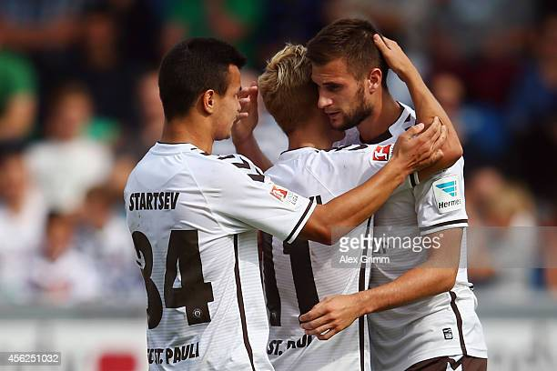 Christopher Noethe of St Pauli celebrates his team's first goal with team mates Marc Rzatkowski and Andrej Startsev during the Second Bundesliga...
