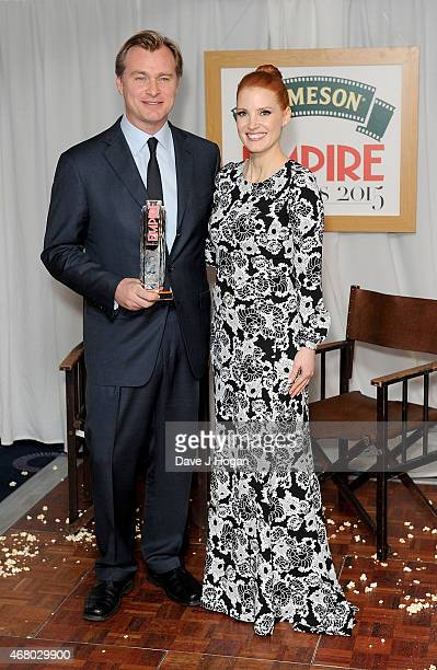 Christopher Nolan winner of the Empire Inspiration award poses with Jessica Chastain in the Winners room at the Jameson Empire Awards 2015 at...