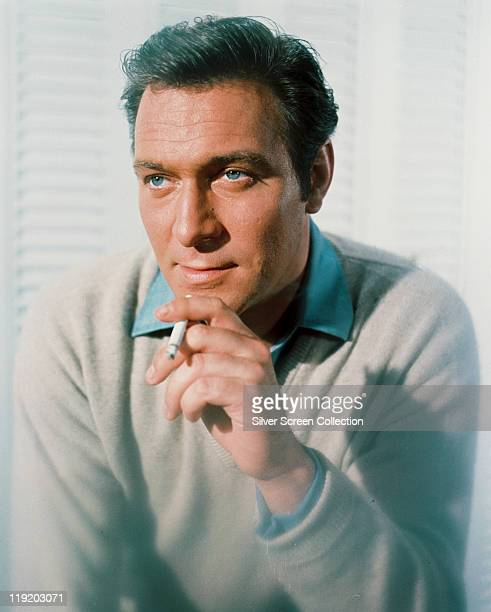 Christopher Plummer Canadian actor smoking a cigarette and wearing grey jumper and blue shirt in a studio portrait against a white background circa...