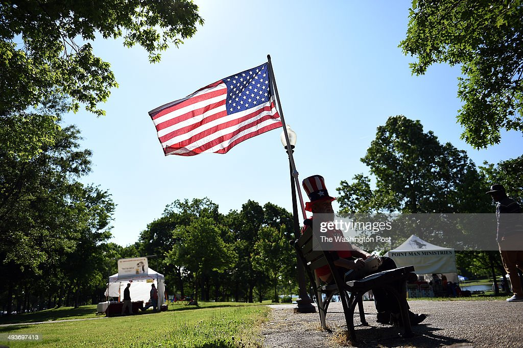 Christopher R. Collopy sits on bench with his US flag near Vietnam Veterans Memorial where ceremonies are held throughout the Memorial Day weekend.