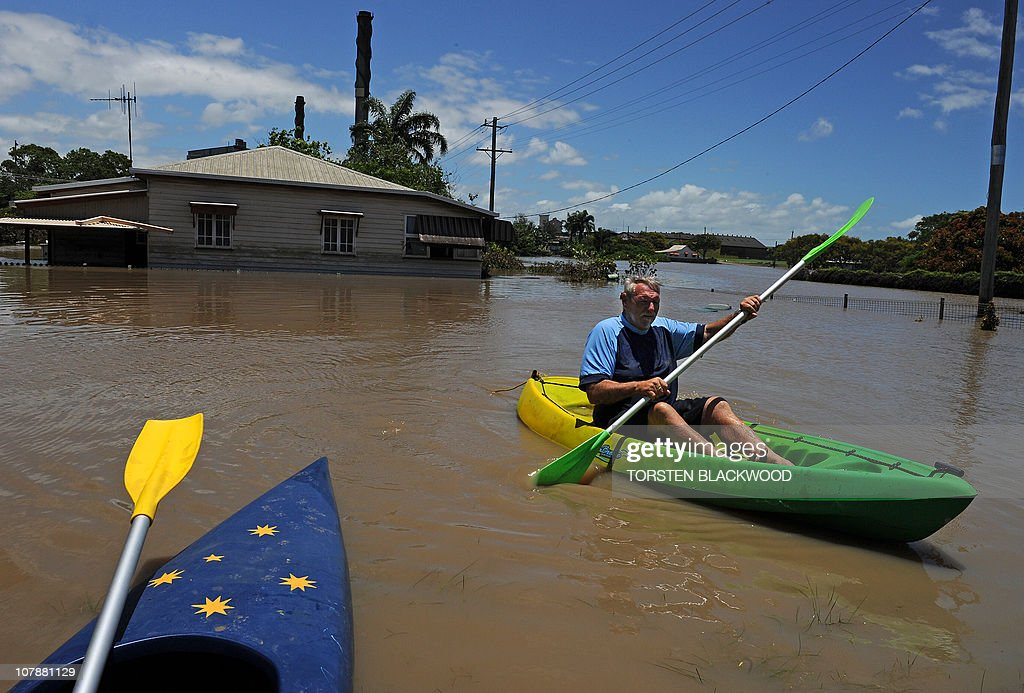Christopher Roth uses a kayak to get to his parents' flooded home (background) in Bundaberg on December 31, 2010. Floods triggered by tropical cyclone Tasha have left entire towns under water and cut off many more over an area the size of France and Germany combined. AFP PHOTO / Torsten BLACKWOOD