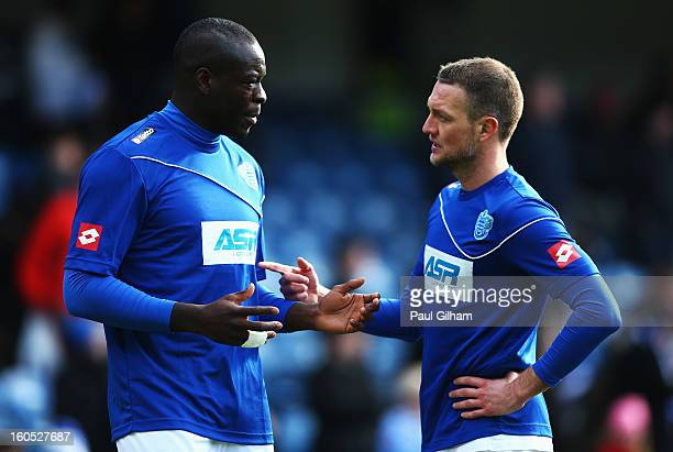 Christopher Samba of Queens Park Rangers talks to his team mate Clint Hill in the warm up prior to the Barclays Premier League match between Queens...