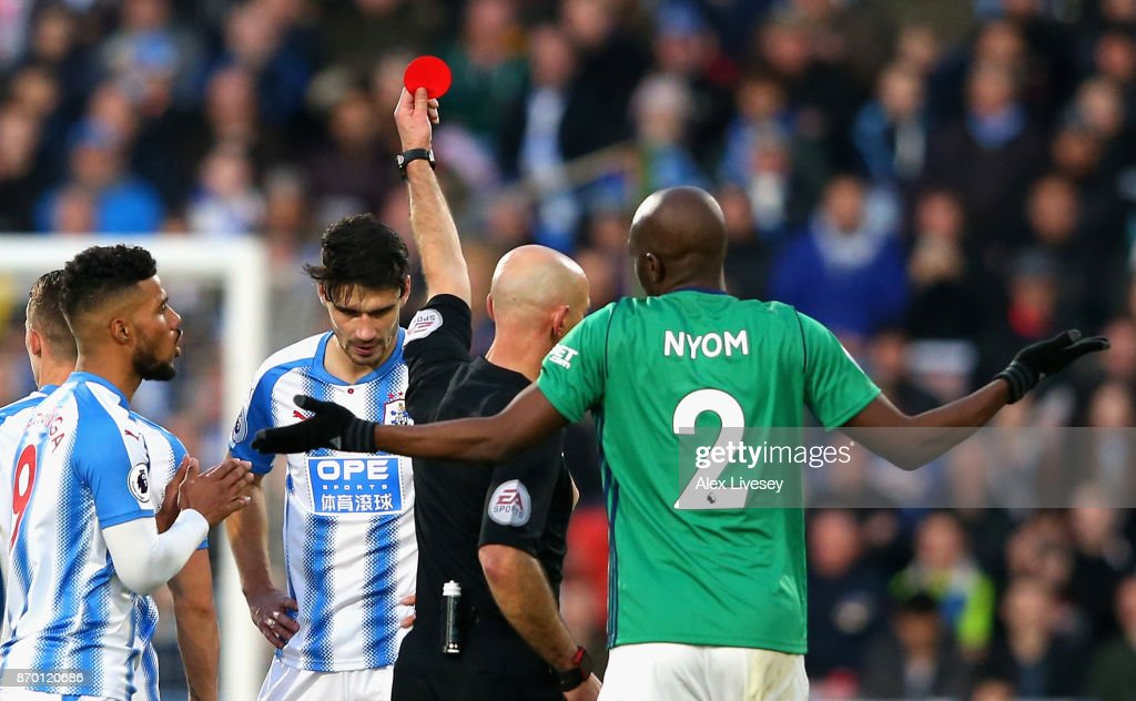 Christopher Schindler of Huddersfield Town is shown a red card by referee Roger East during the Premier League match between Huddersfield Town and West Bromwich Albion at John Smith's Stadium on November 4, 2017 in Huddersfield, England.