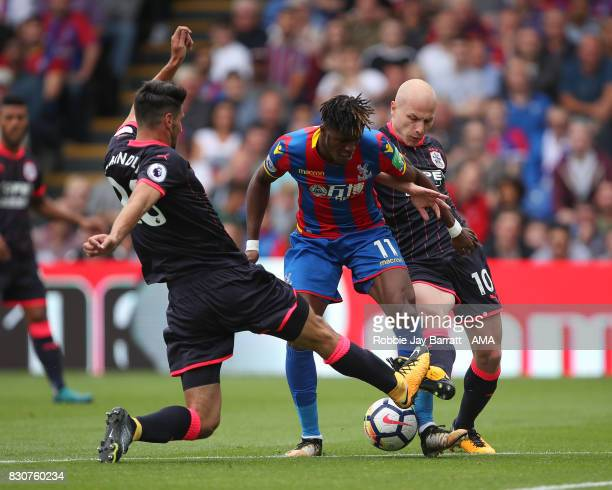 Christopher Schindler of Huddersfield Town Wilfried Zaha of Crystal Palace and Aaron Mooy of Huddersfield Town during the Premier League match...