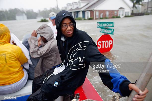 Christopher Smith rides in a boat after being rescued from the rising flood water from Hurricane Isaac in the River Forest subdivision on August 29...