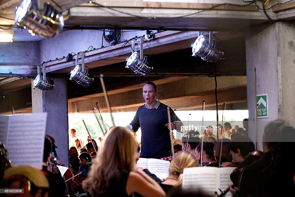 Christopher Stark conducts The Multi-Story Orchestra as they perform Jean Sibelius' 5th Symphony at the Peckham Rye Car Park on June 21, 2014 in London, England. The performance is one of a series that the orchestra will be performing in the South London car park throughout the summer, hoping to bring classical music to new audiences.