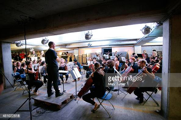 Christopher Stark conducts The MultiStory Orchestra as they perform Jean Sibelius' 5th Symphony at the Peckham Rye Car Park on June 21 2014 in London...